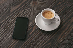 Smartphone with cup of espresso Royalty Free Stock Photos