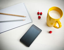 Smartphone, cup of milk and notebook Stock Images