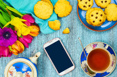 Smartphone and cup of tea with cookies. Composition decorated with flowers on wooden background. Top view. Close-up. Selective focus Royalty Free Stock Images
