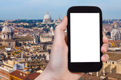 Smartphone with cut out screen and Rome cityscape Royalty Free Stock Images