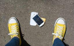 Smartphone démonté au sol devant la personne Images stock
