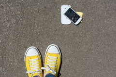 Smartphone démonté au sol devant la personne Photos libres de droits