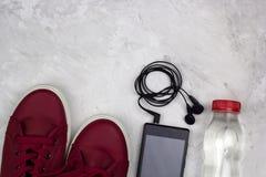 Smartphone d'espadrilles avec les écouteurs et la bouteille de l'eau Photo libre de droits