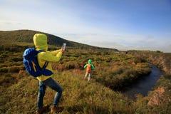 Smartphone d'utilisation d'amis prenant la photo dans la forêt d'automne Photographie stock libre de droits