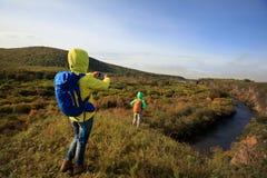 Smartphone d'utilisation d'amis prenant la photo dans la forêt d'automne Image libre de droits