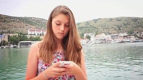 Smartphone d'utilisation de fille sur le fond de mer banque de vidéos