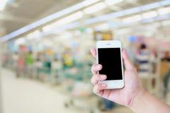 Smartphone d'utilisation de main avec le fond de magasin de supermarché Photo stock