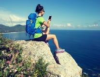 smartphone d'utilisation de randonneur sur le bord de falaise de montagne de bord de la mer Image stock