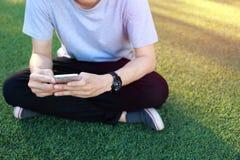 Smartphone d'utilisation de séance d'homme sur le gazon artificiel Photographie stock