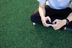 Smartphone d'utilisation de séance d'homme sur le gazon artificiel Images libres de droits