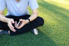 Smartphone d'utilisation de séance d'homme sur le gazon artificiel Image stock