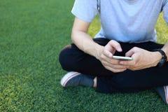 Smartphone d'utilisation de séance d'homme sur le gazon artificiel Photo libre de droits