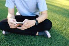 Smartphone d'utilisation de séance d'homme sur le gazon artificiel Image libre de droits