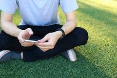 Smartphone d'utilisation de séance d'homme sur le gazon artificiel Photographie stock libre de droits