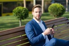 Smartphone d'utilisation d'homme en parc Directeur avec le téléphone portable sur extérieur ensoleillé L'homme d'affaires dans le Images libres de droits