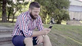 Smartphone da consultação do homem, sentando-se em escadas Slider e bandeja disparados certo filme