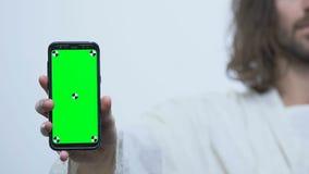 Smartphone da exibição de Jesus Christ com tela verde, aplicação em linha da Bíblia filme