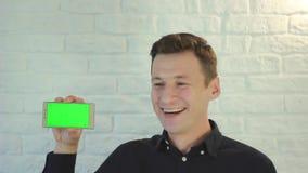 Smartphone da exibição do homem com a tela verde na câmera video estoque