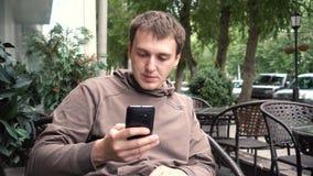 Smartphone da leitura do indivíduo que senta-se no café na rua vídeos de arquivo