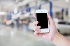Smartphone da posse da mão com centro de serviço de reparações do carro Fotografia de Stock