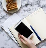 Smartphone da posse da mão da mulher e planejar o dia fotografia de stock