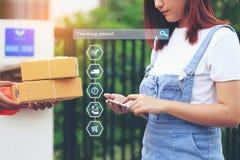 Smartphone da terra arrendada compra, da m?o em linha da mulher e recibo de assinatura do pacote da entrega com o homem de entreg imagens de stock