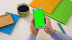 Smartphone da terra arrendada do estudante com tela verde, app em linha da educação, lições video estoque