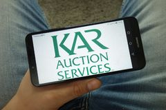 Smartphone da terra arrendada do homem com logotipo da empresa de KAR Auction Services foto de stock