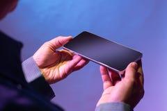 Smartphone da terra arrendada da mão com ambas as mãos foto de stock royalty free