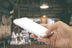 Smartphone da terra arrendada da m?o com a cafetaria velha do borr?o do sum?rio e interior do caf? para o fundo fotos de stock
