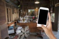 Smartphone da terra arrendada da m?o com a cafetaria velha do borr?o do sum?rio para o fundo imagens de stock royalty free