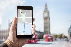 Smartphone da terra arrendada da mão com o mapa na tela em Londres fotos de stock royalty free
