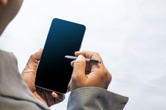 Smartphone da terra arrendada da mão com pena móvel foto de stock