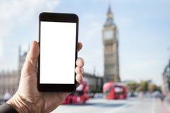 Smartphone da terra arrendada da mão com a tela vazia em Londres imagem de stock royalty free