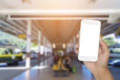 Smartphone da terra arrendada da mão com terminal de ônibus fotos de stock royalty free