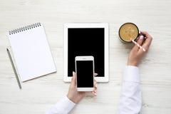 Smartphone dans des mains femelles Espace de travail féminin avec le comprimé, pas Photos stock
