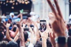 Smartphone dans la main femelle, main avec le téléphone au-dessus de la foule - tir photo stock