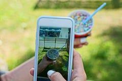 Smartphone dans les mains d'une fille faisant une photo d'une crème glacée colorée dans une tasse dehors en parc image libre de droits