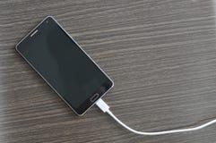 Smartphone, das auf hölzerner Tabelle auflädt Stockbilder