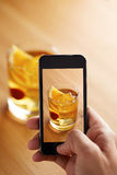 Smartphone, das ein Foto des Cocktails macht Lizenzfreie Stockfotos