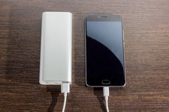 Smartphone, das mit Energiebank auf hölzernem Brett auflädt Stockfoto