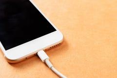 Smartphone, das mit Energiebank auf hölzernem Brett auflädt Stockbilder