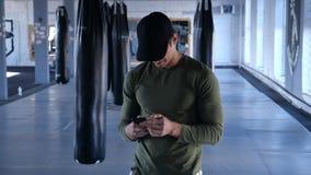 Smartphone das verificações do atleta ao dar certo Ruptura de datilografia do homem novo durante o exercício no gym filme