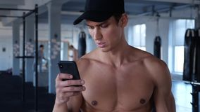 Smartphone das verificações do atleta ao dar certo Ruptura de datilografia do homem novo durante o exercício no gym vídeos de arquivo
