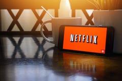 Smartphone, das Wort Netflix auf Holztisch mit Fragment des selektiven Fokus und der Ernte anzeigt lizenzfreies stockfoto