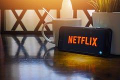 Smartphone, das Wort Netflix auf Holztisch mit Fragment des selektiven Fokus und der Ernte anzeigt stockfoto