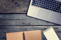 Smartphone de bloc-notes, d'ordinateur portable et d'écran vide sur la table en bois avec f Images libres de droits