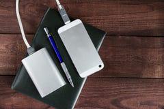 Smartphone de carga con la batería externa portátil gris en woode Imágenes de archivo libres de regalías