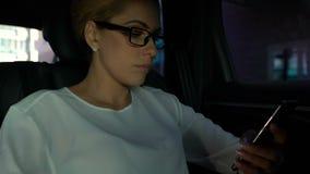 Smartphone de charla de la empresaria rica en el asiento trasero del automóvil, comunicación almacen de video