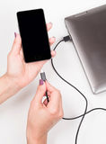 Smartphone de conexión de la mujer a un cuaderno para accionar Imagen de archivo